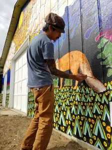 Chris Huang painting a mural
