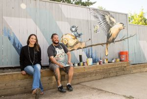 Patrick Maxcy with homeowner in front of mural