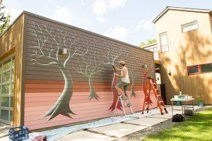 Tony Zellaha painting a mural for Creative Neighborhoods